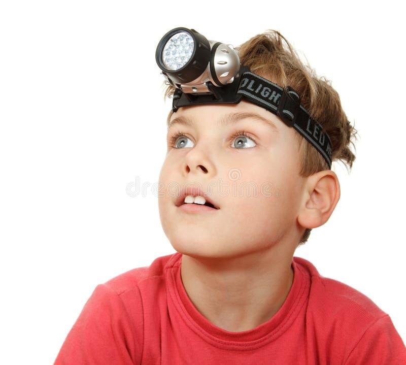 Junge mit Taschenlampe auf seinem Kopf auf Weiß lizenzfreie stockfotografie