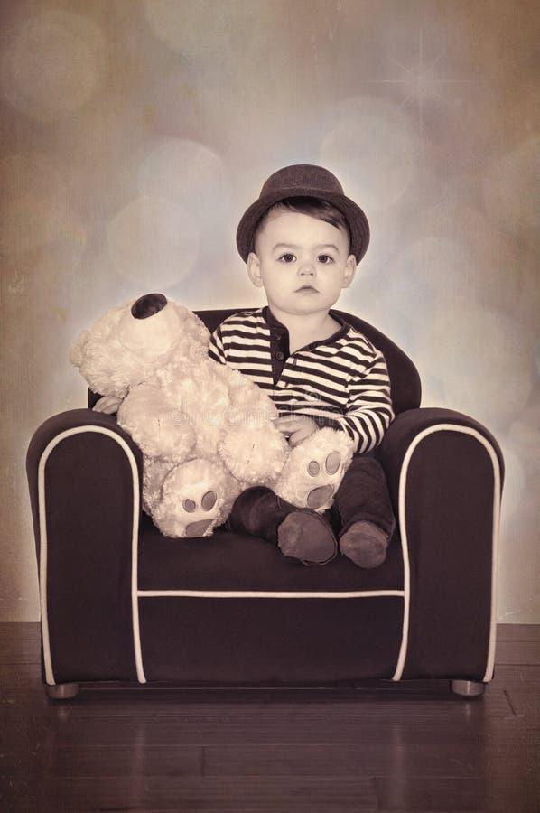 Junge mit Teddybären im Stuhl mit Weinlese Sepiaaffekt stockbilder