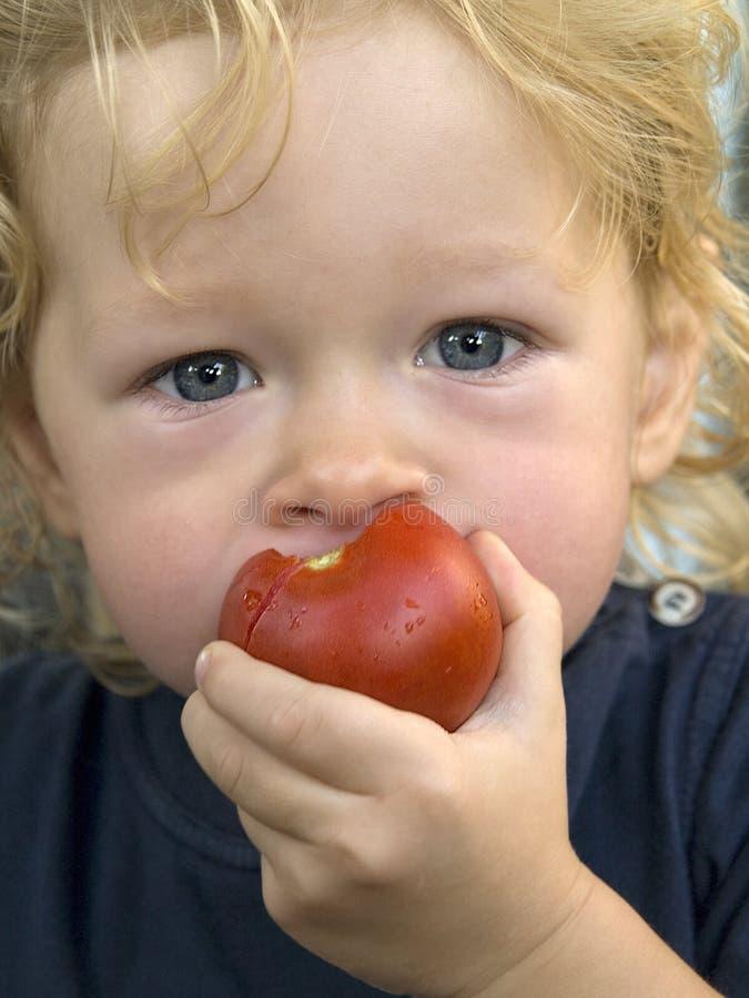 Junge mit Tomate stockbilder