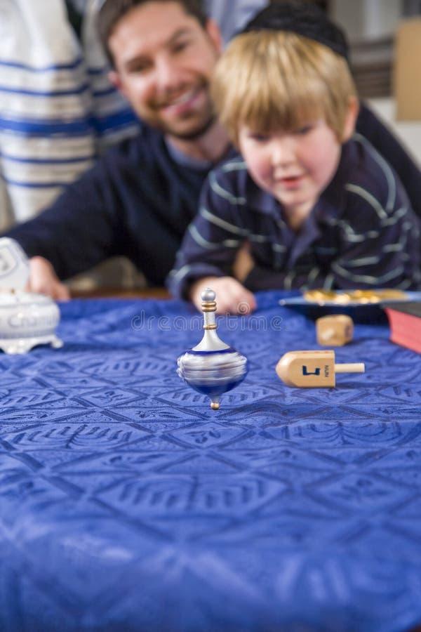 Junge mit Vater spinnendem dreidel stockbild