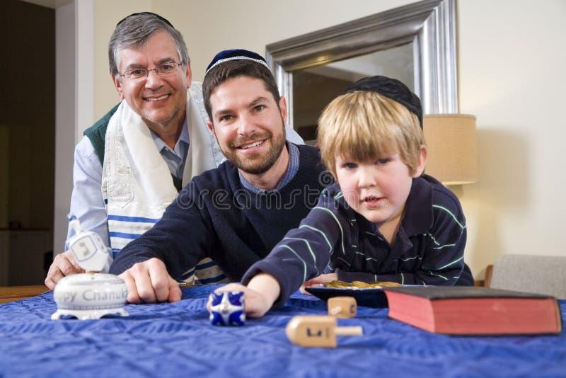 Junge mit Vater und Großvater spinnendem dreidel stockfoto