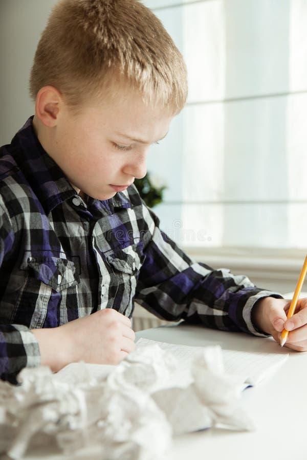 Junge mit Verfasserblock kämpfend mit Hausarbeit stockfoto