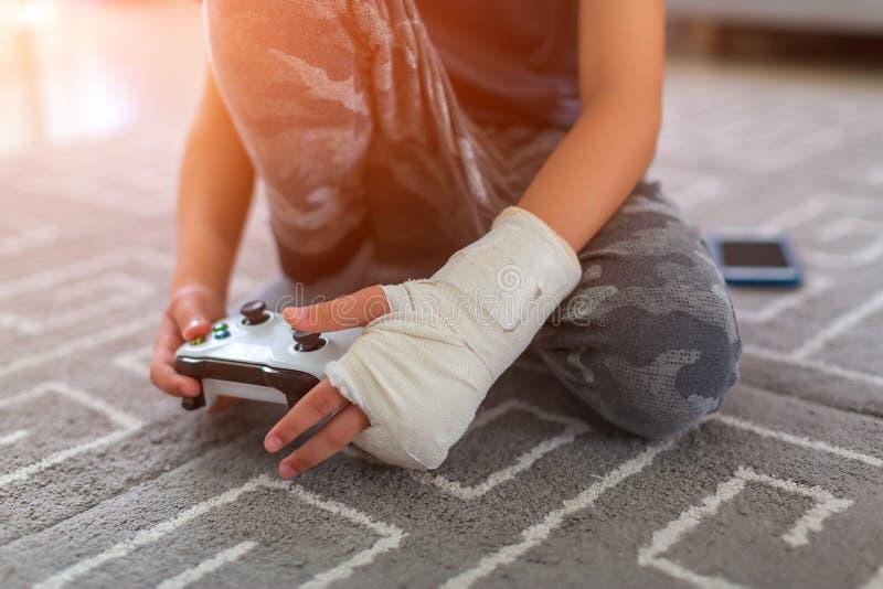Junge mit Verletzung zu Hause yonge Videogamersh?nde unter Verwendung eines gamepad lizenzfreie stockbilder