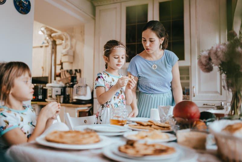 Junge mitfühlende Mutter und ihre zwei kleine Töchter, die Pfannkuchen mit Honig am Frühstück in der gemütlichen Küche essen stockfotos