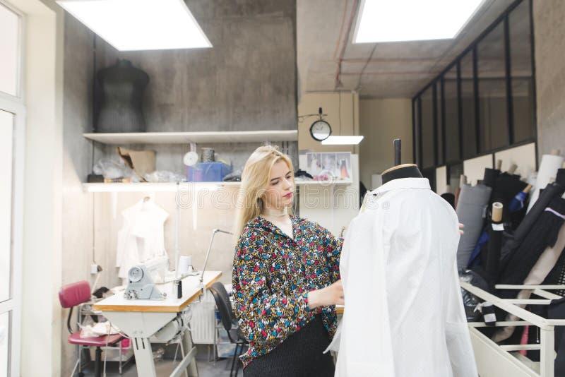 Junge Modedesignerstellung im Studio und Versuchen auf Kleidung auf einem Mannequin lizenzfreie stockfotos