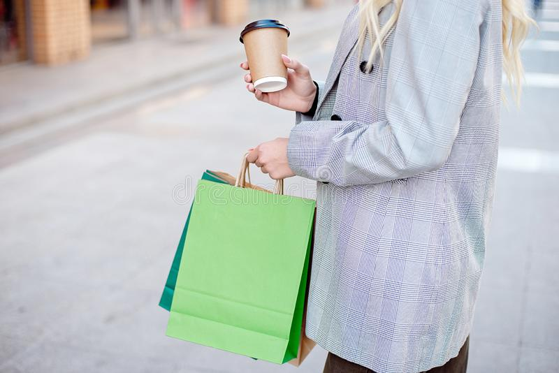 Junge Modefrau der Nahaufnahme mit den Einkaufstaschen, die draußen nahe Schaufenstergeschäftsfenstern auf der Straße stehen stockbilder