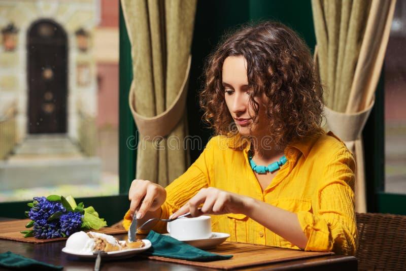 Junge Modefrau, die Kuchen am Restaurant isst stockbild