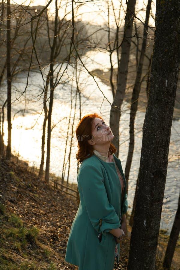 Junge Modefrau, die Sonnenuntergang nahe einem Fluss in Bauska, Lettland, 2019 sich entspannt und genießt stockbilder