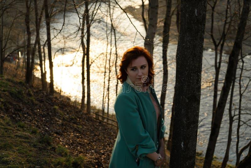 Junge Modefrau, die Sonnenuntergang nahe einem Fluss in Bauska, Lettland, 2019 sich entspannt und genießt lizenzfreies stockfoto