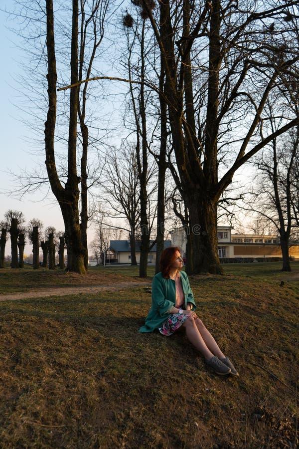 Junge Modefrau, die Sonnenuntergang nahe einem Fluss in Bauska, Lettland, 2019 sich entspannt und genießt stockfotos