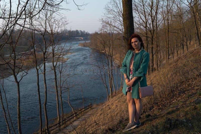 Junge Modefrau, die Sonnenuntergang nahe einem Fluss in Bauska, Lettland, 2019 sich entspannt und genießt stockbild