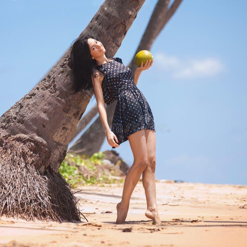 Junge Modefrau entspannen sich auf dem Strand Gl?cklicher Insellebensstil Prety-Frauen-Griffkokosnu? unter Palme auf dem tropisch lizenzfreie stockfotos