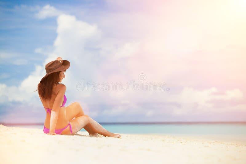 Junge Modefrau entspannen sich auf dem Strand Gl?cklicher Lebensstil Wei?er Sand, blauer Himmel und Kristallmeer des tropischen S lizenzfreie stockfotos