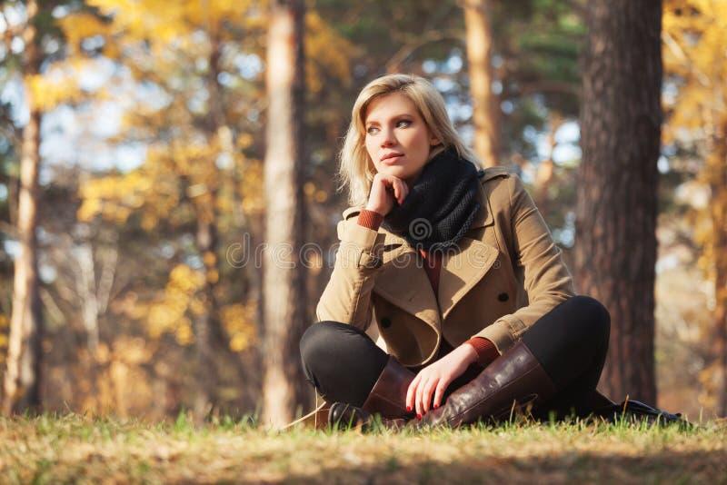 Junge Modefrau im beige Mantel, der auf Gras im Herbstpark sitzt lizenzfreie stockbilder