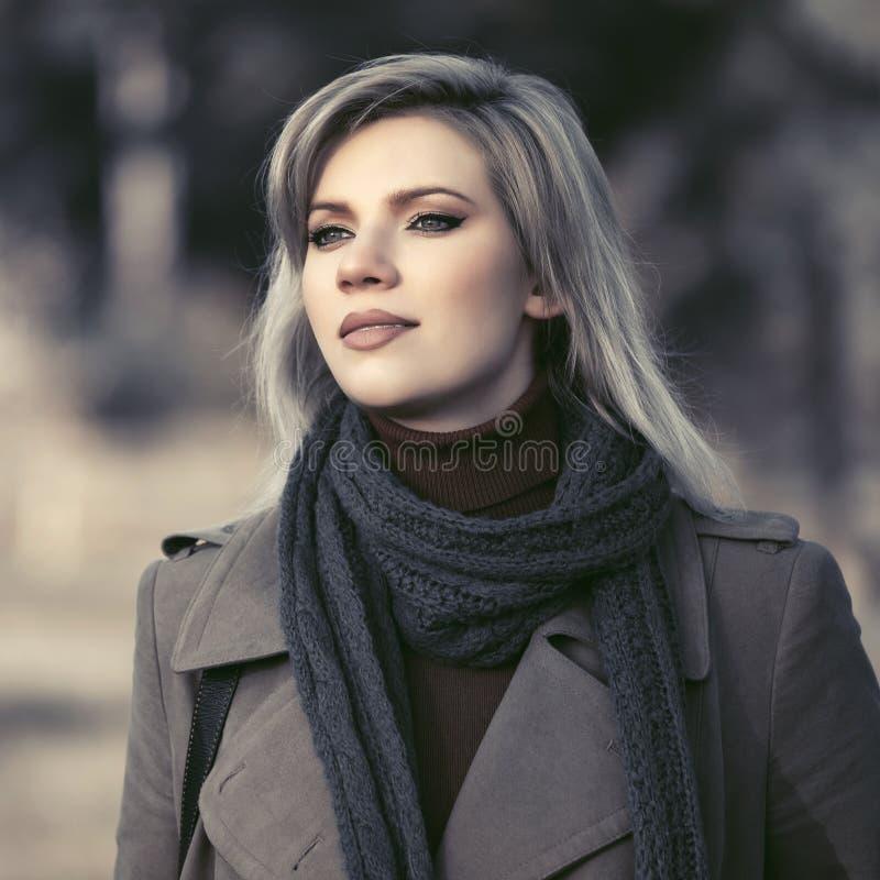Junge Modefrau im klassischen beige Mantel gehend in Herbstpark stockbilder
