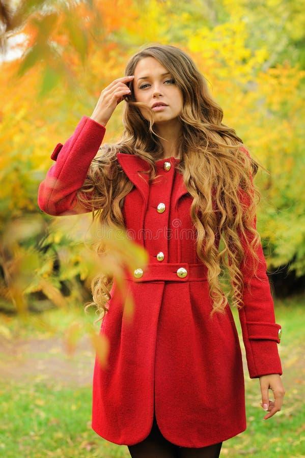Junge Modefrau kleidete im roten Mantel im Herbstpark an lizenzfreies stockbild