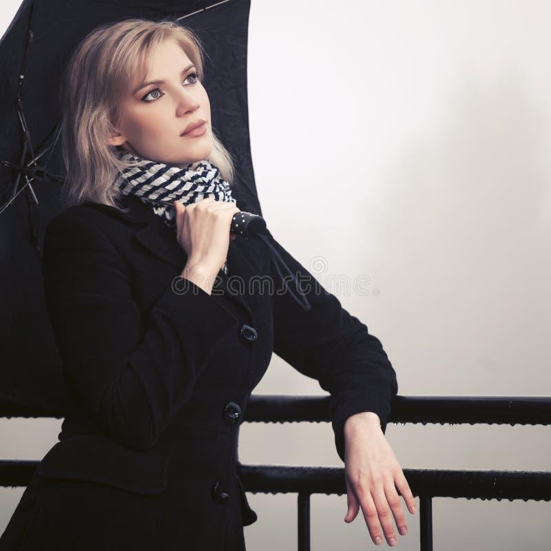 Junge Modefrau mit dem Regenschirm, der auf draußen mit der Eisenbahn befördern sich lehnt lizenzfreie stockbilder