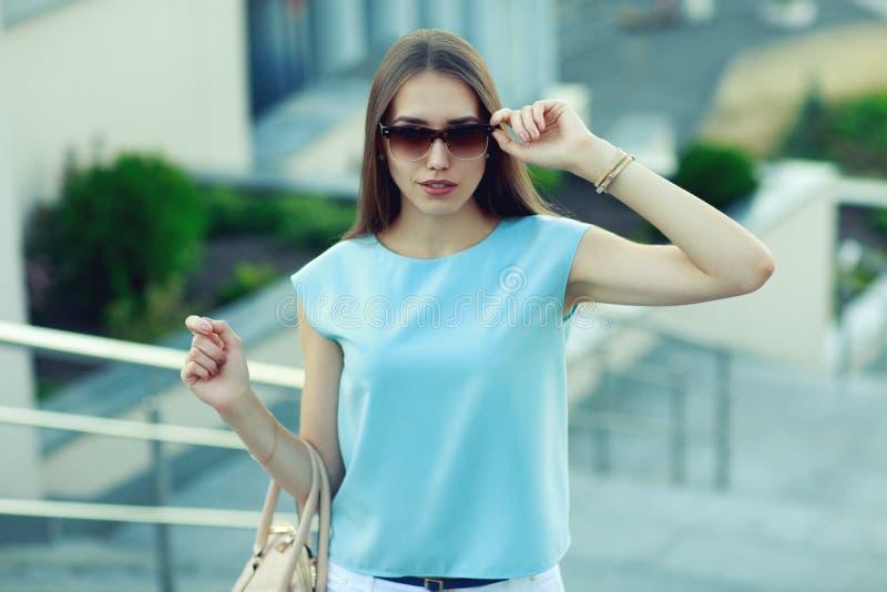 Junge ModeGeschäftsfrau in der Sonnenbrille auf einer Stadtstraße lizenzfreie stockbilder