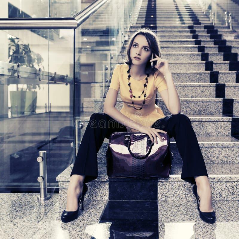 Junge ModeGeschäftsfrau, die am Handy im Büroinnenraum spricht stockfotos