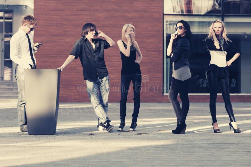 Junge Modeleute, die Handys auf Stadtstraße verwenden stockbild