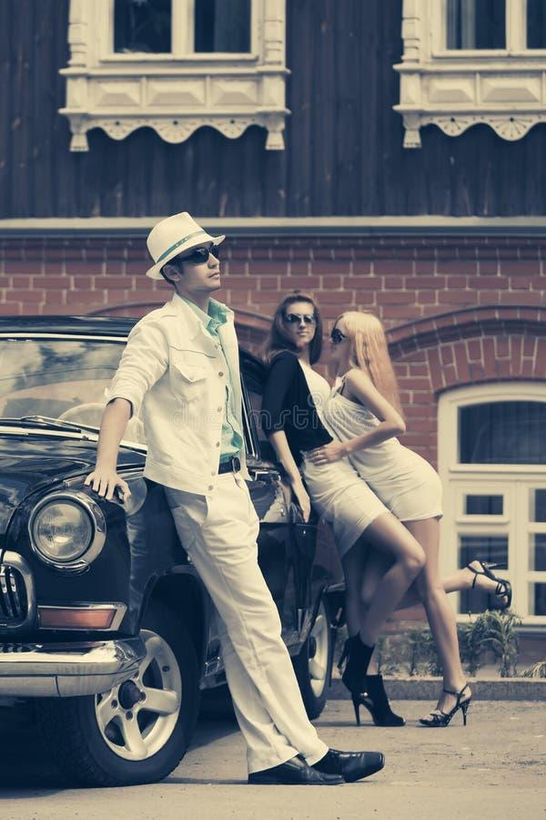 Junge Modeleute nahe bei Retro- Auto auf Stadtstraße lizenzfreie stockfotografie