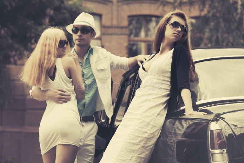 Junge Modeleute nahe bei Retro- Auto auf Stadtstraße stockfoto