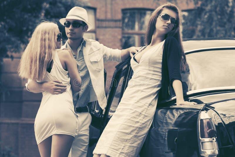 Junge Modeleute nahe bei Retro- Auto in der Stadtstraße lizenzfreie stockfotografie