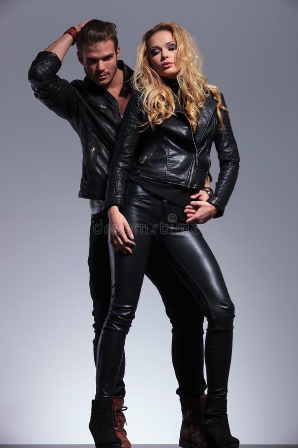 Junge Modepaare in lederner clother Aufstellung lizenzfreie stockfotografie