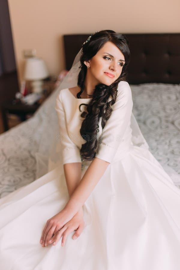 Junge moderne aufgeregte Braut, die auf Bett im Hochzeitskleid sitzt und von ihrem neuen Eheleben träumt lizenzfreie stockfotos