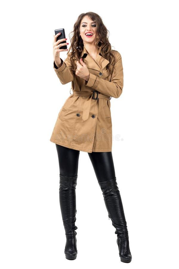 Junge Modeschönheit im Herbst kleidet das Halten des Handys, der Foto macht stockbilder