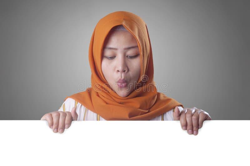 Junge moslemische Frau, die hinter leerem wei?em Brett l?chelt stockfotografie