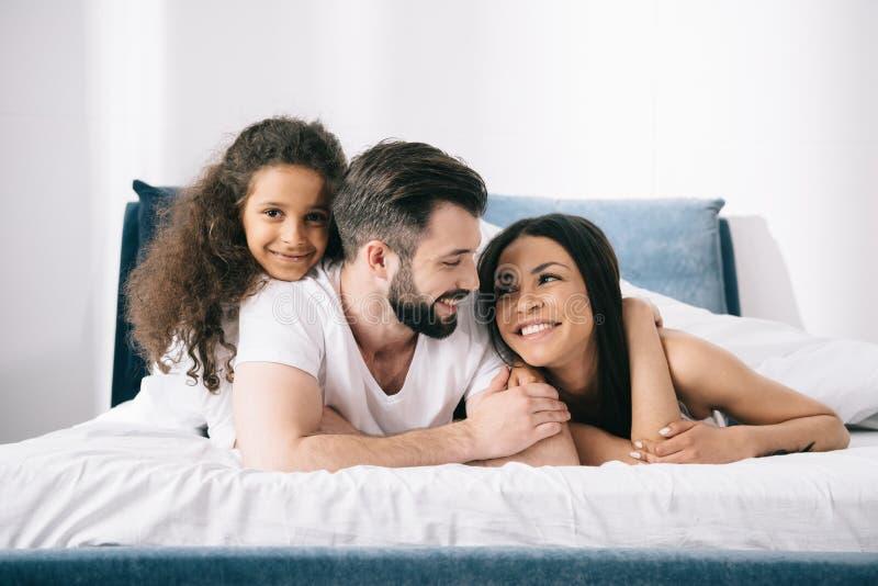 Junge multiethnische Familie mit einem Kind, das zusammen im Bett liegt lizenzfreie stockfotos