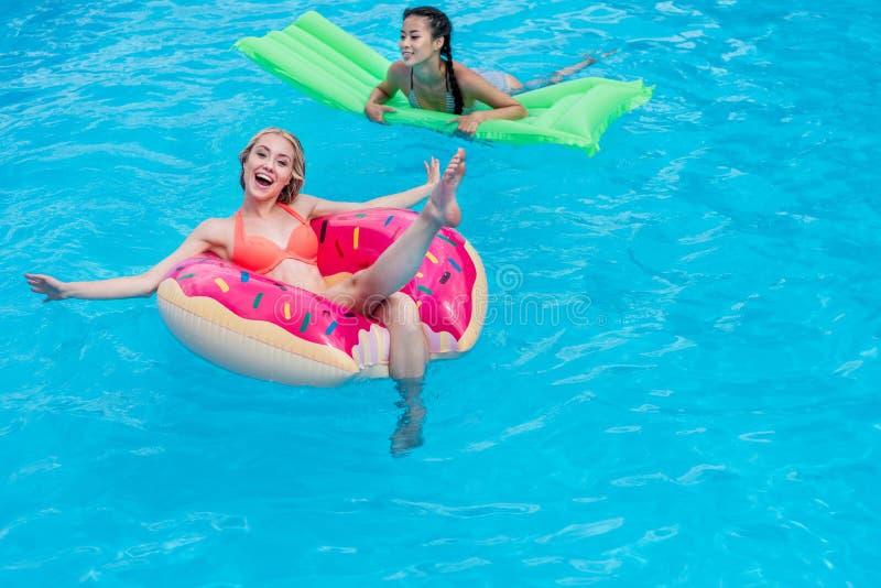 Junge multiethnische Frauen, die auf aufblasbare Matratzen im Swimmingpool schwimmen lizenzfreie stockfotos