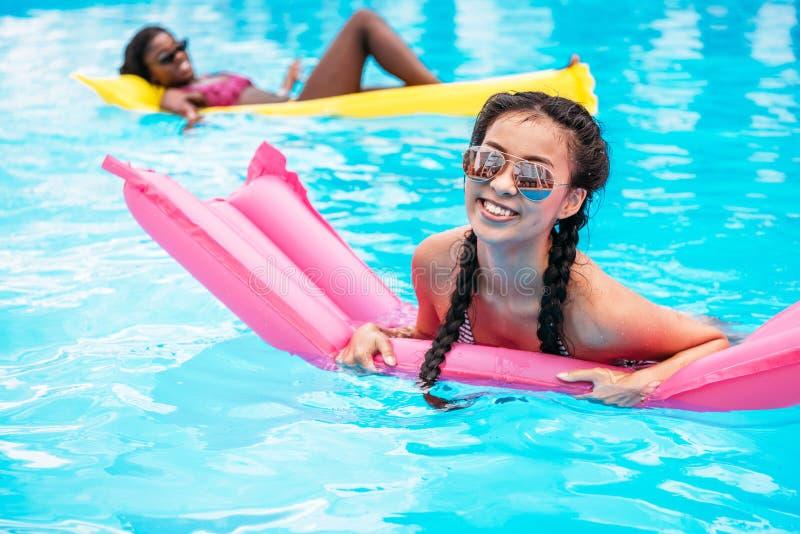 Junge multiethnische Frauen, die auf aufblasbare Matratzen im Swimmingpool schwimmen stockfotografie