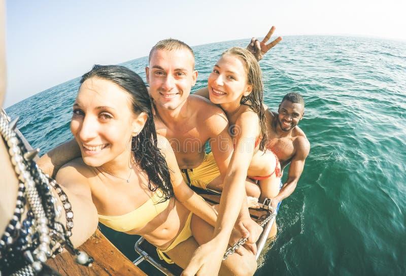 Junge multiethnische Freunde, die selfie nachdem dem Schwimmen auf Segelboot nehmen lizenzfreie stockfotos