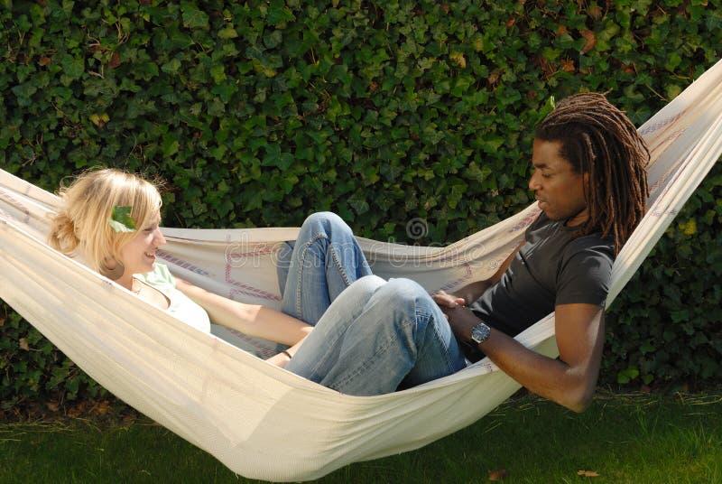 Junge multiethnische Paare in der Hängematte lizenzfreies stockbild