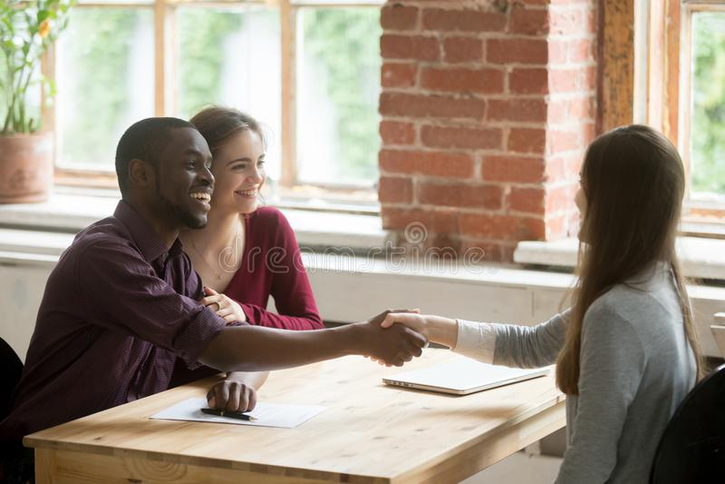 Junge multiethnische Paare, die Hände mit Immobilienagentur rütteln lizenzfreies stockfoto