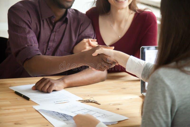 Junge multiethnische Paare, die Hände mit Immobilienagentur rütteln lizenzfreie stockbilder