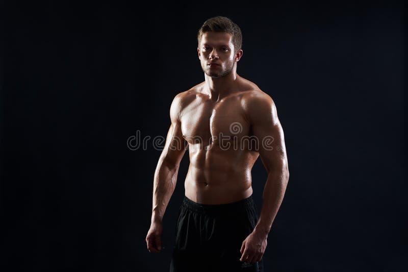 Junge muskulöse Sitzsportleraufstellung hemdlos auf schwarzem backgroun stockbild