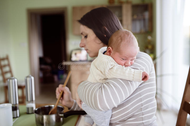 Junge Mutter in der Küche, die den Babysohn, kochend hält stockfotos
