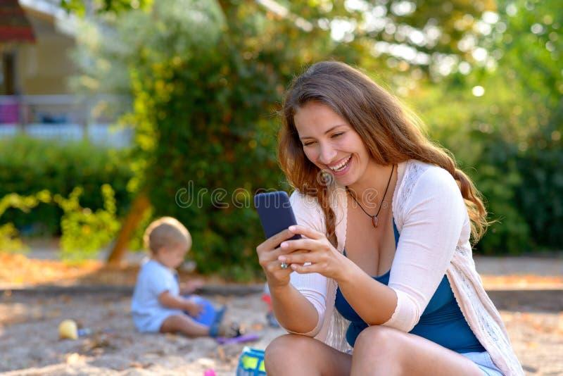 Junge Mutter, die über eine Textnachricht lacht lizenzfreies stockbild