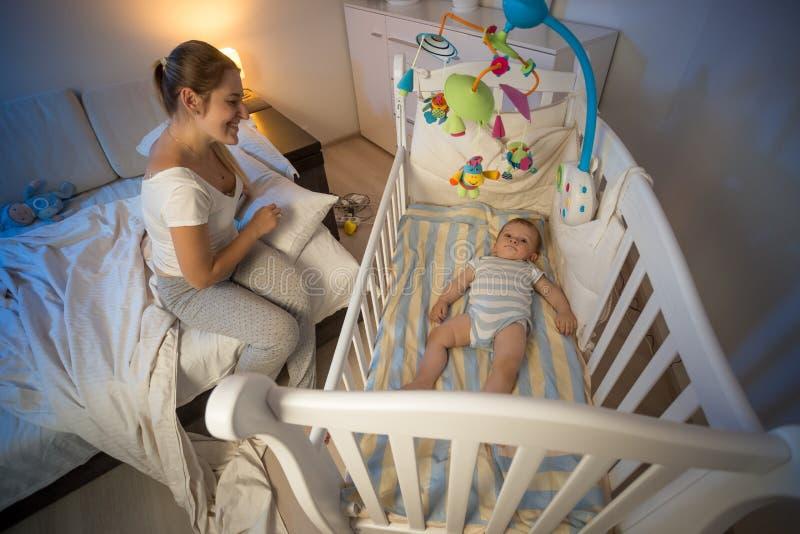 Junge Mutter, die auf Bett sitzt und auf ihrem Babysohn liegt im Feldbett schaut stockfoto