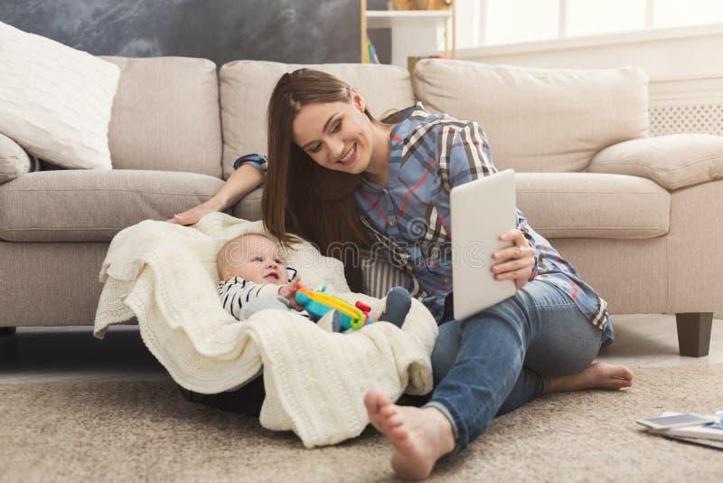 Junge Mutter, die Baby beim Arbeiten hält lizenzfreie stockbilder