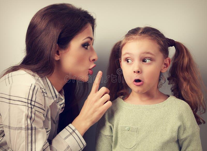 Junge Mutter, die dem Finger das Ruhezeichen zu ihrem surprisi zeigt lizenzfreies stockfoto