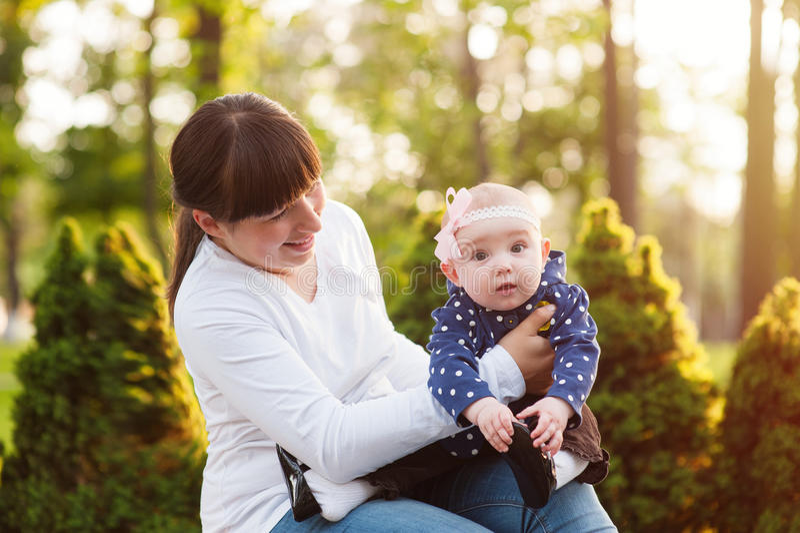 Junge Mutter, die ein Baby und Wege im Park trägt stockbild