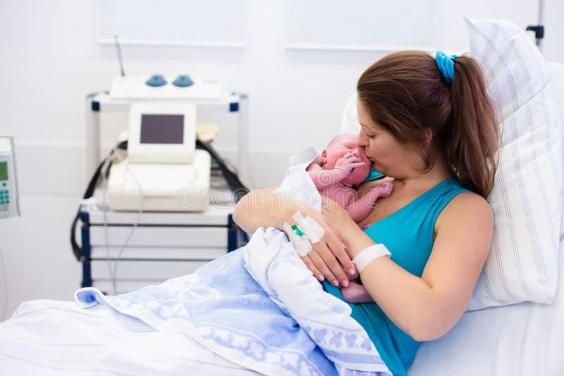 Junge Mutter, die einem Baby entbindet lizenzfreie stockfotos