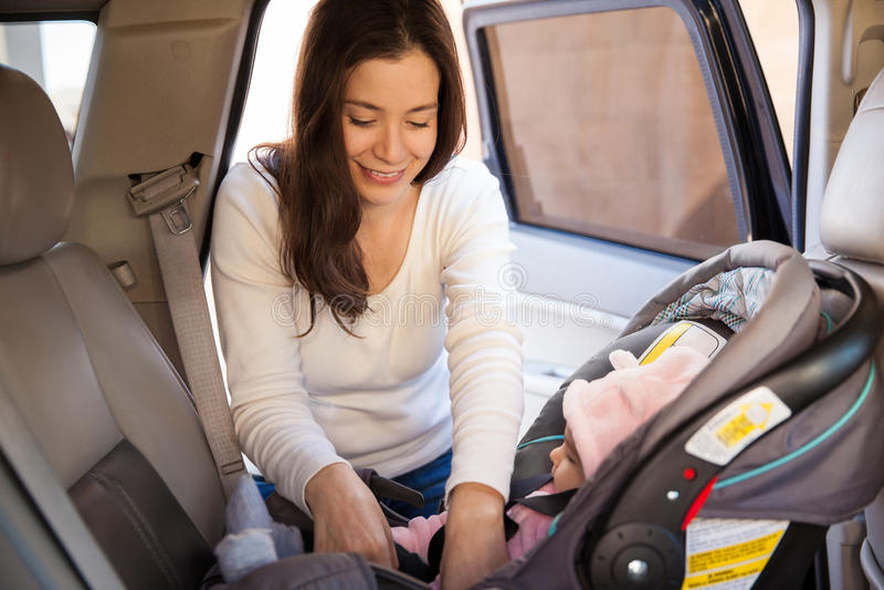 Junge Mutter, die einen Kinderautositz sichert stockfoto