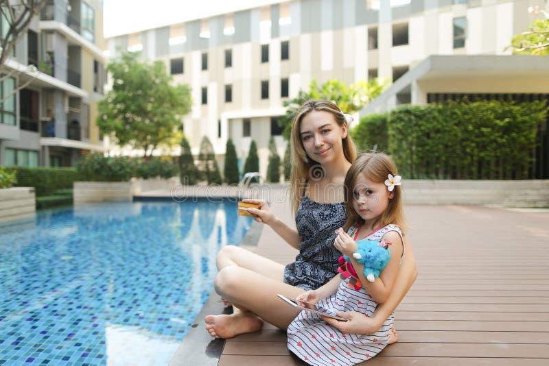 Junge Mutter, die an Ferien mit Laptop nahe Swimmingpool arbeitet lizenzfreie stockfotografie
