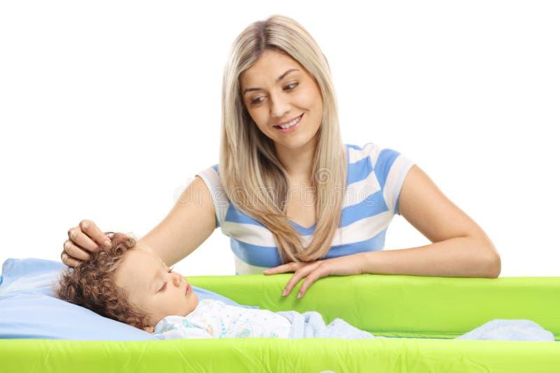 Junge Mutter, die ihr Baby beim Schlafen in einem Feldbett streicht lizenzfreies stockbild