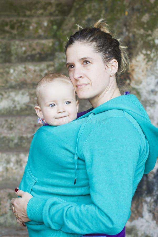Junge Mutter, die ihr Baby im Riemen trägt stockbild